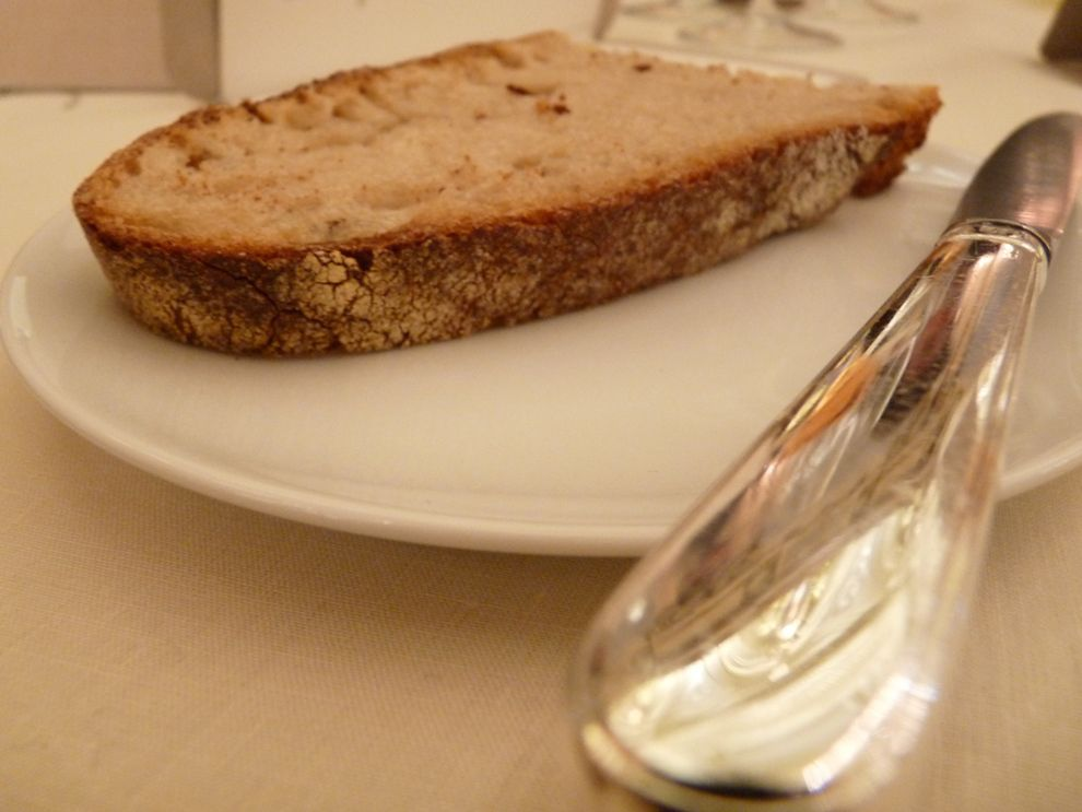 Tranche de pain à base de farine de meule, à la texture compacte.