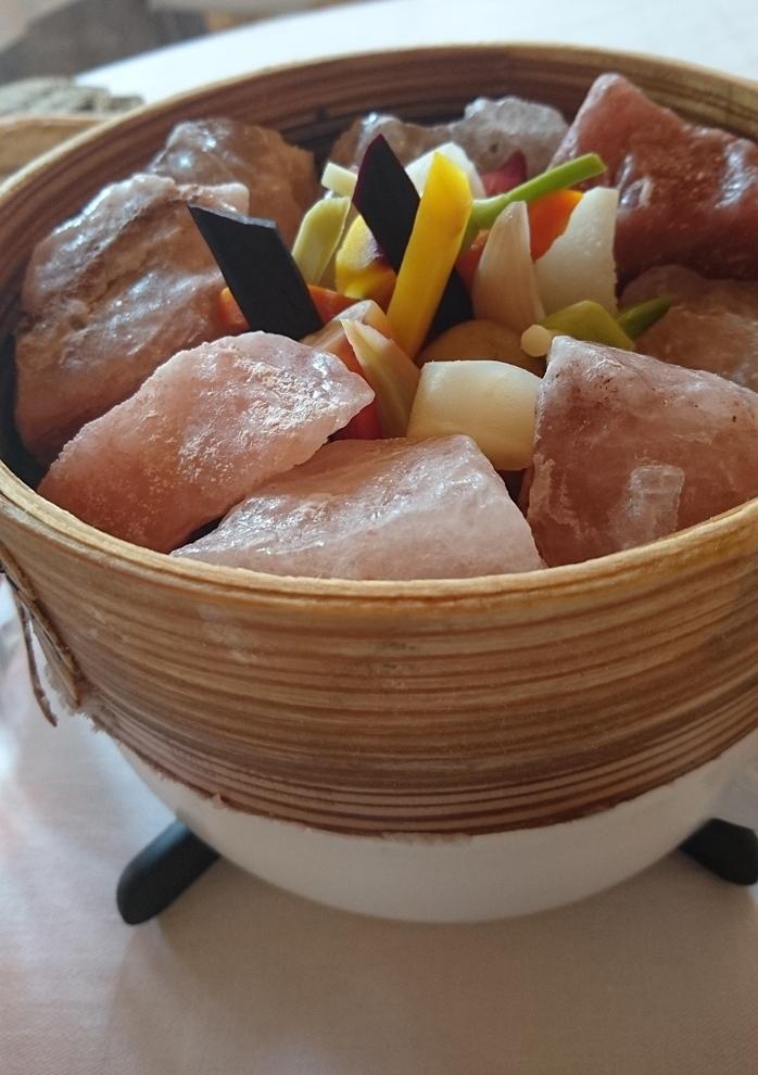 Cocotte de légumes bio de Créance, en Normandie (carottes jaunes, violettes, oranges, artichaut, betterave chioggia...). Réalisée dans l'esprit du partage, les petits légumes disposés entre des cristaux de sel rose de l'Himalaya sont cuits à la minutes et trempé dans un condiment à l'olive noire_ © Clémence Rouyer