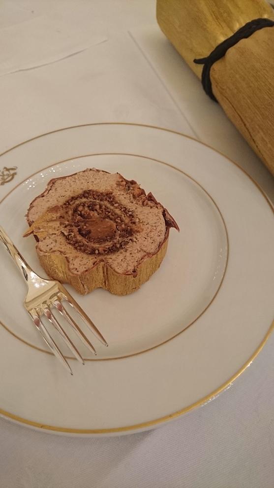 La bûche Noisette: chocolat brossé à l'or, gâteau roulé noisette, coeur tendre caramel, mousse noisette, nœud croquant au chocolat.
