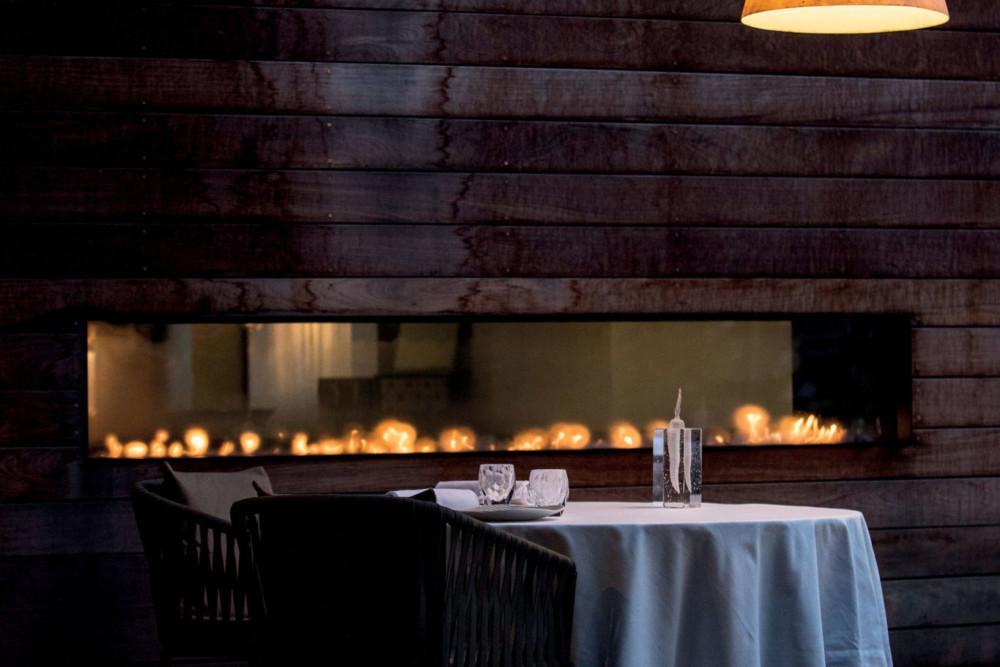 Matériaux bruts pour ambiance délicate dans la toute nouvelle salle de restaurant. Sur les murs, le bois noircit à mesure qu'il s'approche des fl ammes. Celle des fourneaux, celle de la passion qu'entretiennent le chef et son équipe.