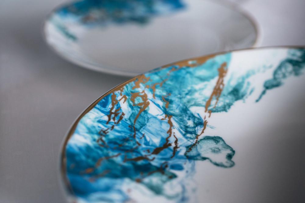 À TABLE L'eau du lac fait des vagues jusque dans les assiettes. Des créations Bernardaud uniques, déposées aux côtés de serviettes brodées, datant de l'époque Bise.