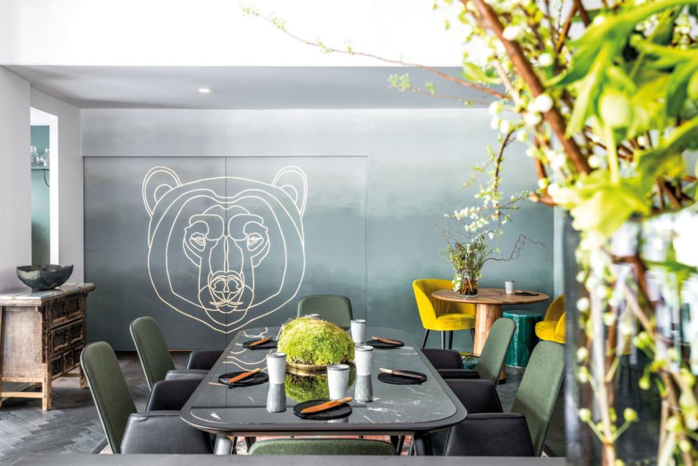 Au fond de la salle, une grande porte coulissante arbore une illustration de tête d'ours et s'ouvre sur la cuisine.